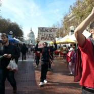 With San Francisco's opulent City Hall in the background, National Day of Action protesters march through throngs of UN Plaza Farmers Market shoppers on Oct. 22. Though the shoppers seemed mostly disinterested, they must have read the placards. – Photo: Zo Khumalo