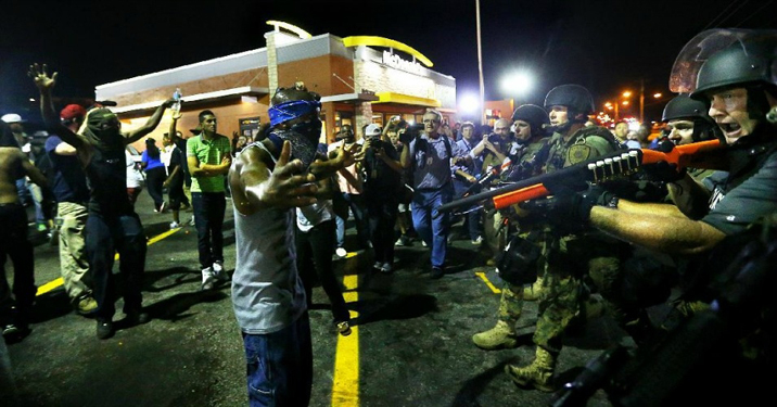 """Police officers move in to arrest protesters as they push and clear crowds out of the West Florissant Avenue area in Ferguson, Mo., early Wednesday, Aug. 20,"" reads the AP caption. – Photo: Curtis Compton, Atlanta Journal-Constitution"