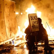 A protester sits in front of a street fire during a demonstration in Oakland following the grand jury decision not to indict the cop who murdered Michael Brown. – Photo: Stephen Lam, Reuters