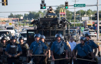 A police sniper targets protesters during the months-long rebellion following the police murder of Michael Brown in Ferguson, Mo., last year.