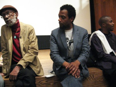 """With the visit of Sam Greenlee, celebrated – and persecuted – for his film, """"The Spook Who Sat by the Door,"""" on April 8, 2012, not long before he died, the Oakland International Film Festival made history. Here are Greenlee, David Roach and The People's Minister of Information JR at the Oakland Museum, where the festival was held that year."""