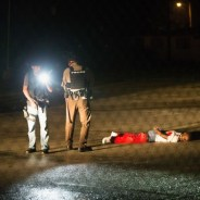 "Tyrone Harris Jr., 18, who his father says was ""very close"" to Michael Brown, lies critically wounded by cops on the ground one year to the day after Brown's death, Aug. 9, 2015. The photo is eerily similar to that of Michael Brown as he lay dead on the ground for four and a half hours after being shot eight times by cop Darren Wilson."