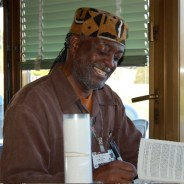 Baba Jahahara signs his books in Europe following an interview by Henry Gomba of London- and Uganda-based Black Star News. – Photo: Claudette Perry
