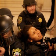 "Fellow journalist Joel Angel Juárez writes: ""Photojournalist Gabriella Angotti-Jones, with El Tecolote and CCSF's The Guardsman, gets shoved by San Francisco sheriff deputies while covering a protest at San Francisco City Hall on Friday, May 6, 2016. Angotti-Jones had her press credentials visible on her person. Angotti-Jones and three other journalists (including myself) were assaulted by SF deputy sheriffs while reporting during Friday's ‪#‎Frisco5‬‬/ ‪#‎Frisco500‬‬/ ‪#‎hungerforjusticesf‬‬ protest."" – Photo: Noé Serfaty"