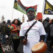 "Baba Jahahara Amen-RA Alkebulan-Ma'at stands with thousands of other reparationists on Emancipation Day, 1 Mosiah (August) 2016, for three minutes of silence for the Ancestors on the Westminster Bridge in London, England. Behind them is the British Parliament – House of Commons and House of Lords – with the ""Big Ben"" clock tower, where a major rally was later held. Petitions demanding reparations were also delivered to No. 10 Downing Street, the official residence of the British prime minister."