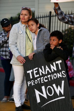 Anna Gonzalez, with her daughter Aidsa, 9, and son Nelson, 7, listens to speakers as tenants rally at the Creekview Apartments in Richmond on Thursday, Oct. 6. More than 100 renters are being evicted from the apartments. Tenants are demanding that the owner, PMI Properties, halt evictions and let the remaining tenants stay in the recently refurbished apartments. – Photo: Jane Tyska, Bay Area News Group