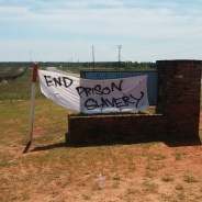 """On April 9, 2016, supporters holding a rally outside Holman Prison to draw attention to Free Alabama Movement's campaign to end prison slavery placed a banner on top of the sign identifying """"W.C. Holman Correctional Facility."""""""