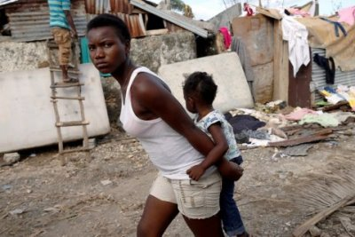 In the town of Jeremie, Haiti, on Oct. 7, a young woman carrying a child looks none too happy about the devastation caused by Hurricane Matthew. In Cuba, the same storm caused damage but no deaths because its government is not controlled by the U.S. and cares about the people. – Photo: Carlos Garcia Rawlins, Reuters