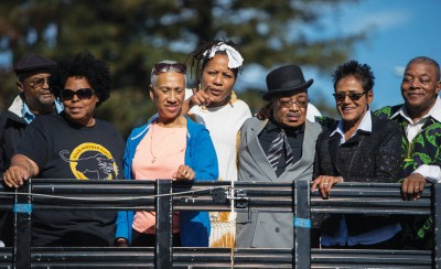At Bobby Hutton Grove are members of Bobby Hutton's family, BPP 50th Host Committee members and, in the middle, Oakland City Council President Lynette McElhaney, who made the renaming of part of the park to Bobby Hutton Grove happen. Elaine Brown and Bobby's brother are on the right. – Photo: Malaika Kambon