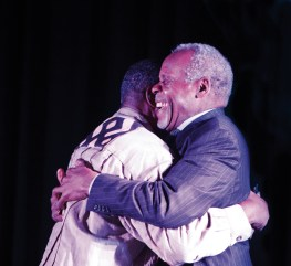 A warm embrace between old friends Eddie Conway and Danny Glover reflects determination to unite and live the legacy. – Photo: Malaika Kambon