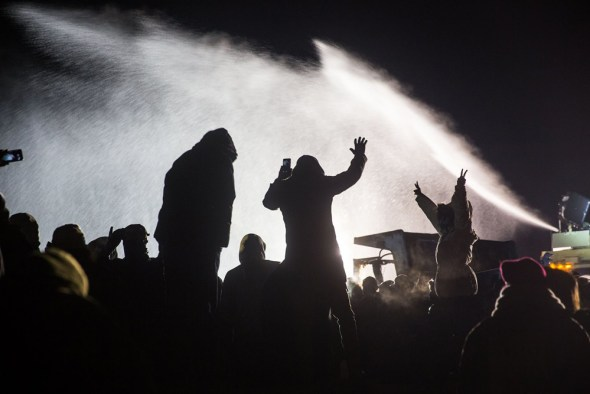 In below-freezing weather Sunday night, Nov. 20, law enforcement deployed tear gas, water cannons, percussion grenades and rubber bullets against hundreds protesting the Dakota Access Pipeline. News reports confirm more than 300 people have been injured. Many were knocked to the ground after being hit in the head by rubber bullets. One woman may lose her arm. – Photo: Sacred Stone Camp