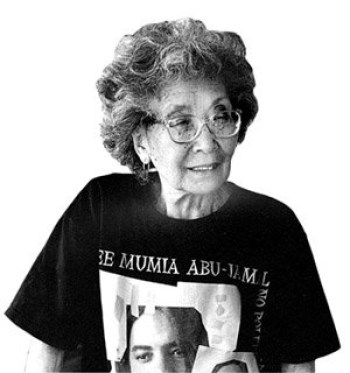 "Colin Kaepernick, who likes to indicate his political positions with his t-shirts, could wear a ""Free Mumia"" shirt like the one shown here. It is worn by the incomparable political prisoner supporter Yuri Kochiyama. Yuri, a close friend of Malcolm X, who was in the hall when he was assassinated, rushed to the stage and cradled his head in her lap as he died. She later moved to Oakland, where she made a full time job of supporting political prisoners, mentoring young people and encouraging everyone who dares oppose criminalization to silence dissent. As a youngster, she had been interred in a concentration camp during World War II."
