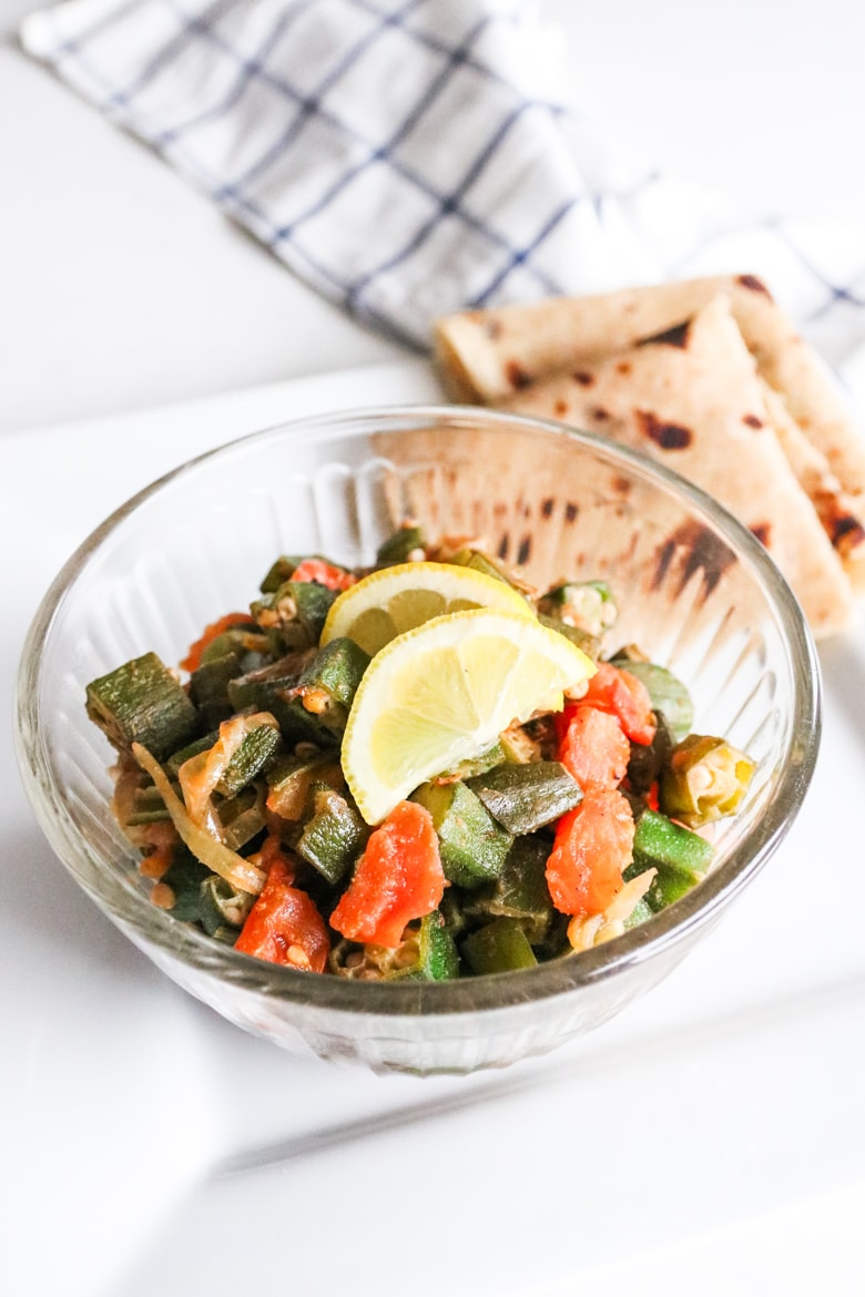 bowl of spicy okra with onions and tomatoes with roti