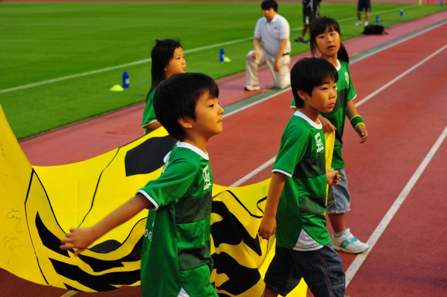 children march the Verdy flag off