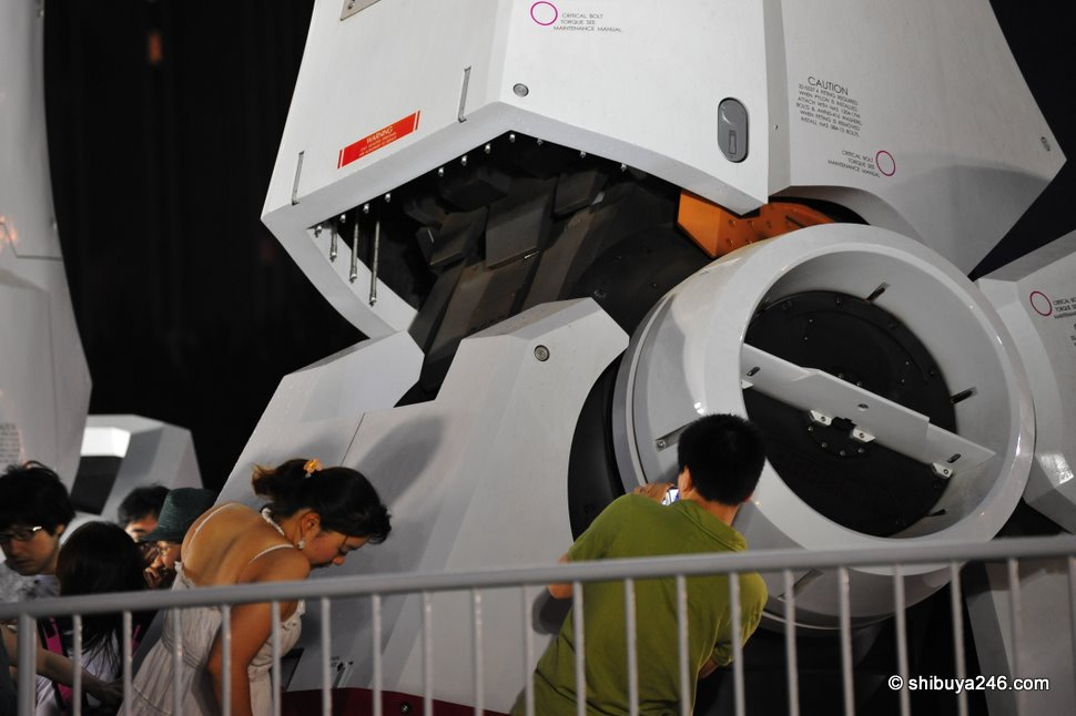 A few people risk being trodden on by Gundam here as they take a photo of his boots