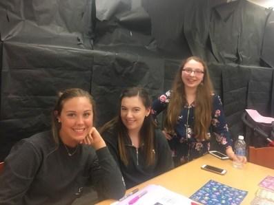 "From left to right; Kaitlyn Keefer, senior, Lexi Evon, senior, Melanie Gillott, junior help out the kids at the ""sticker table."""