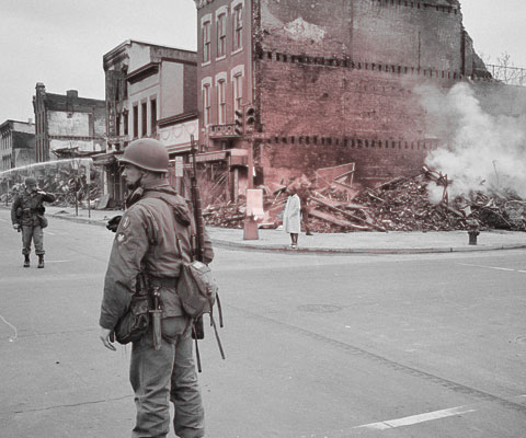 Soldier stands guard in front of building destroyed by riots in Washington, D.C. following the assassination of MLK. (Image: public domain)