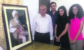 Kulbir Singh Sangherha and his family members stand in front of Baba Bhagat Singh's portrait at Desh Bhagat Yadgar Hall in Jalandhar