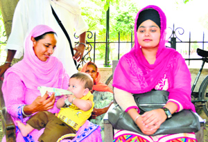 Baba's wife with their infant son outside the court. Tribune photo