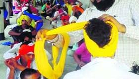 Tejinder Singh ties turban on a volunteer at a gurdwara in Mansa.