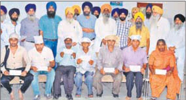 Kin of the eight missing Punjab natives who went missing in Iraq with cheques handed over by the SGPC in Amritsar