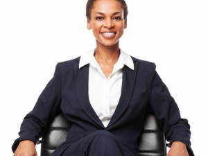 Portrait of a successful African American businesswoman sitting on office chair. Vertical shot. Isolated on white.