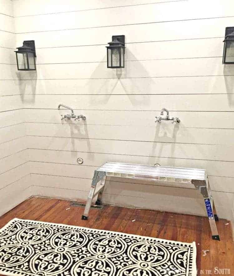 Shiplap bathroom with black and white rug seeded glass light fixtures and wall mount faucets