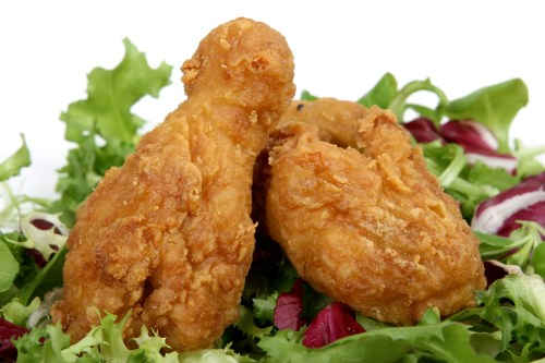 Deep fried spring chicken in golden lemon batter with salad, macro close up isolated on white with copy space