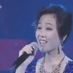 One of the Moranbong Band's six jewel-bedecked singers at the ensemble's debut on July 6, 2012 | Image via Korea Central TV