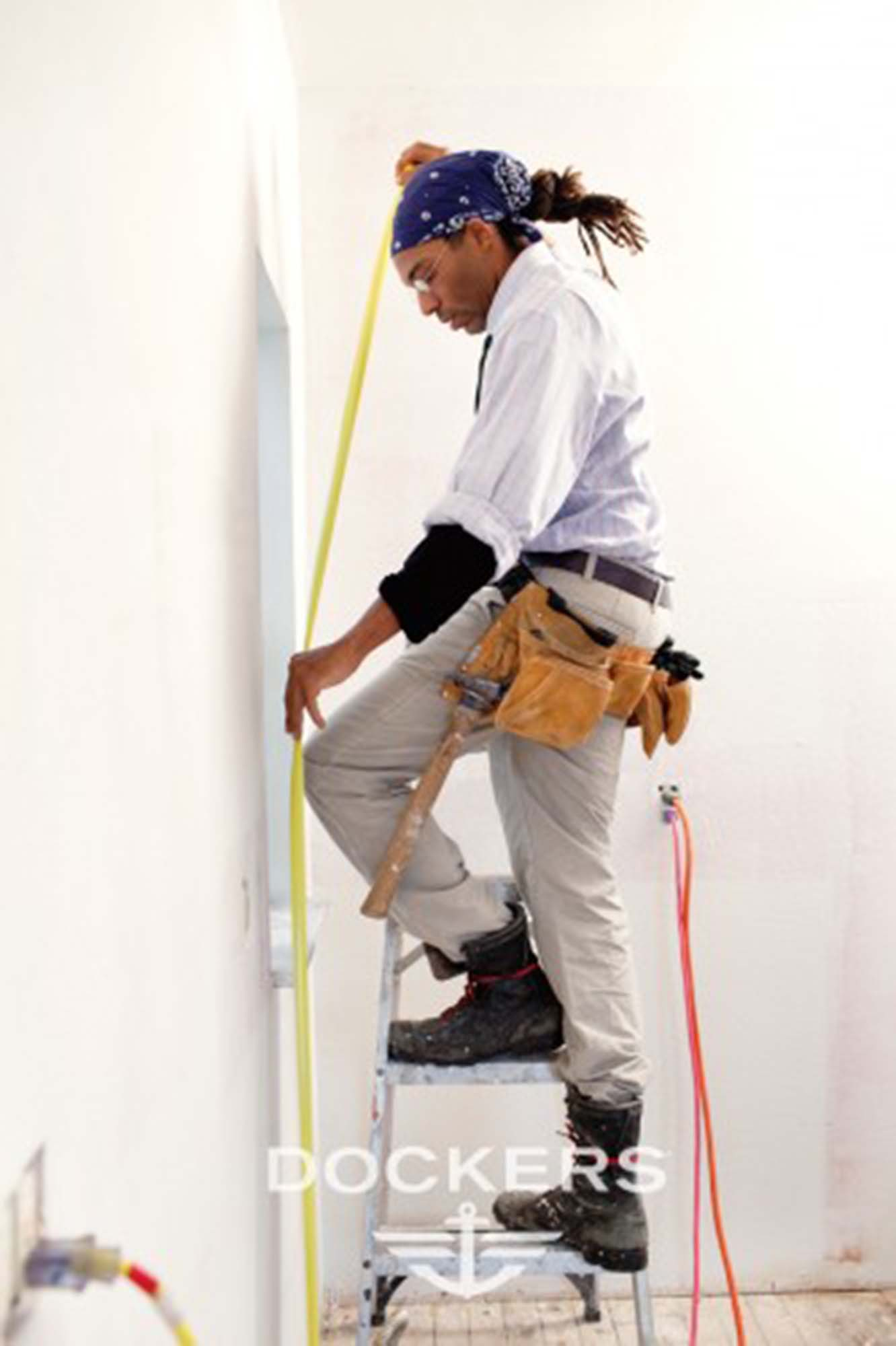 Man on a ladder measuring a wall