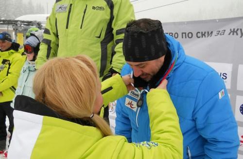 """Мая Христоскова, изпълнителен директор на """"ЮЛЕН"""" връчва бронзовия медал на фото редактора на SkiMagazine Николай Дончев."""