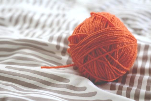 orange yarn ball on bedsheet