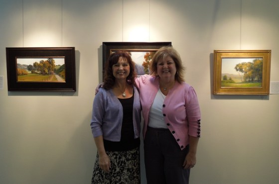 Linda Mutti and Sheryl Knight between their paintings at Studios on the Park