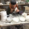 An old Palestinian man paints pottery at a local glass blowing business outside of Hebron.