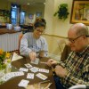 Junior Mary Locascio plays a game of cards with a Brighton Gardens member. Photo by Paloma Dickey