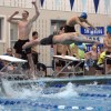 Junior Patrick Hornung cheers as senior Zack Holbrook dives off the block before their opponents. Holbrook was the forth and final swimmer in the 200-yard freestyle relay. Photo by James Wooldridge