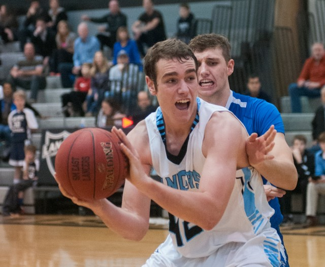 Junior Joey Wentz looks to pass as he is guarded by Rockhurst's senior Noah Spencer. Photo by James Wooldridge