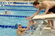 After placing 1st in the 500 yard Freestyle, Freshman Aidan Holbrook high fives his teammate Mitchell Kerr. Holbrook receives a time of 4:49.36. Photo by Annie Lomshek.