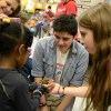 Senior Emily Biegelsen and Junior Warren Van Ryzin supervises as a girl holds a tarantula. Photo by Morgan Browning