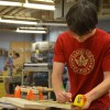 Sophomore Eric Blom takes measurements for the sizing of his woodshop project. Photo by Annie Lomshek.