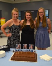 The three seniors take a picture with their specially made cake. Photo by Annie Lomshek.
