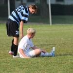 Junior Joe McGuire helps senior Hayes Hendricks after a fall. Photo by Abby Walker