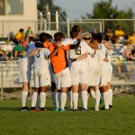 The team huddles before the start of the game.  Photo by Tess Iler
