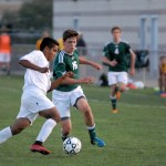Senior Gian Roque tries to keep the ball away from a South player.  Photo by Tess Iler