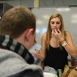 Senior Caroline Beck takes a break from handing out food to snack on the food. Photo by Callie McPhail