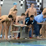 Teammates watch anxiously as junior Hayden Linscott swims the final lap of the 400 yard freestyle relay. Photo by Haley Bell