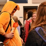 Senior Tyler Armer shows his friends the tail on his onesie on Tuesday's pajama day. Photo by Morgan Browning