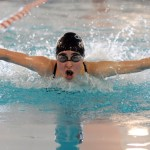 Freshman Lucy Patterson competes in the 100 yard butterfly. Photo by Haley Bell