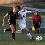 Senior Adalaide Kline blocks out a Shawnee Mission West player as she tries to keep control of the ball. Photo by Haley Bell