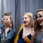 Graduates Hallie Haynes, Chloe Standford, Emily Loveland and Hannah Ream pose for pictures in a photo booth. Photo by Porter Carroll